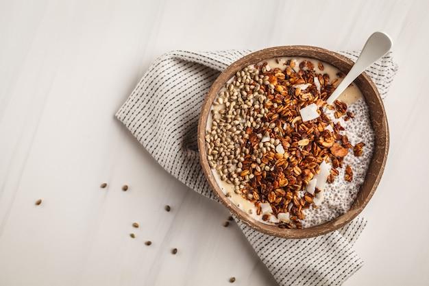 Un tazón de batido con granola, pudin de chia y semillas de cáñamo en un recipiente de cáscara de coco.