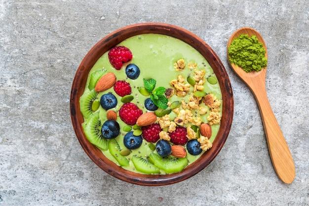 Tazón de batido hecho de té verde matcha con bayas frescas, nueces, semillas con una cuchara para un desayuno vegano saludable