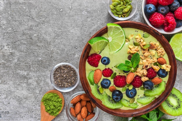Tazón de batido hecho de té verde matcha con frutas frescas, bayas, nueces, semillas con una cuchara para un desayuno de dieta saludable