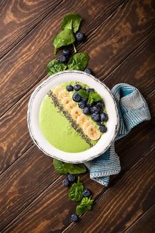 Tazón de batido verde de desintoxicación de desayuno de plátano y espinaca sobre superficie de madera