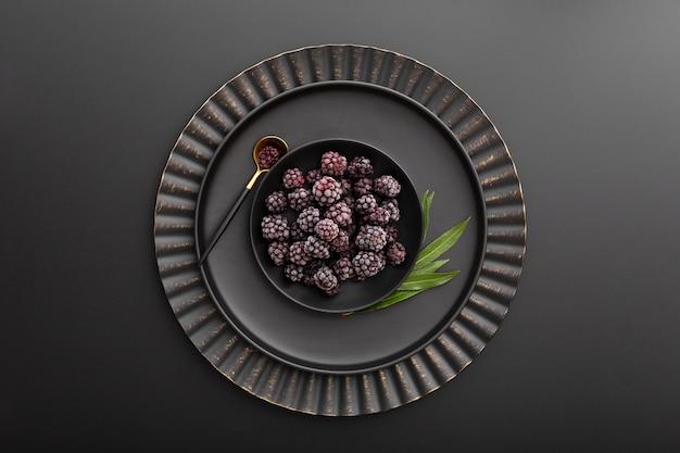 Tazón de blackberry en un plato oscuro sobre un fondo oscuro