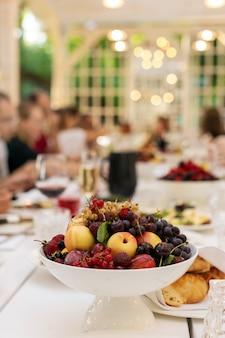 Tazón blanco con fruta en mesa festiva