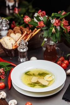 Un tazón blanco lleno de deliciosa sopa de pollo con fideos.