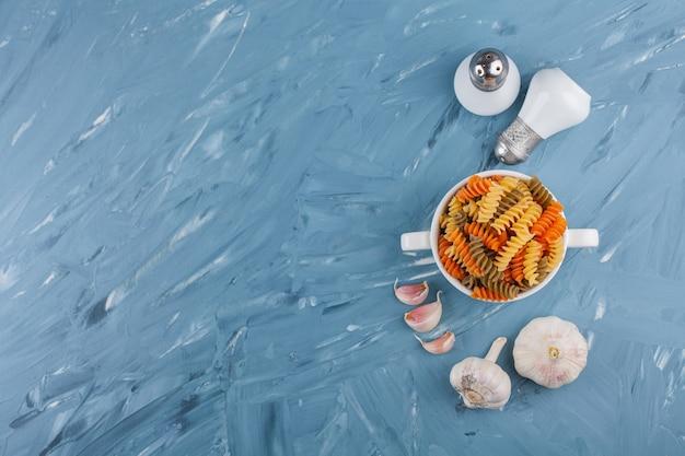 Un tazón blanco de pasta espiral cruda multicolor con ajo y especias.