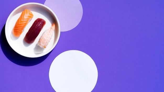 Tazón blanco con sushi sobre un fondo azul con círculos blancos