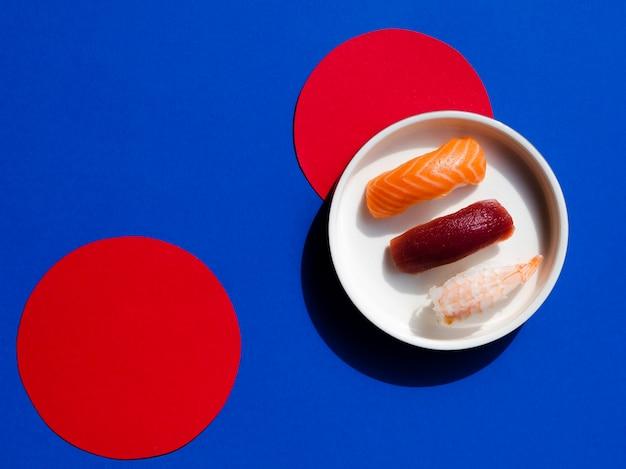 Tazón blanco con sushi sobre un fondo azul y rojo