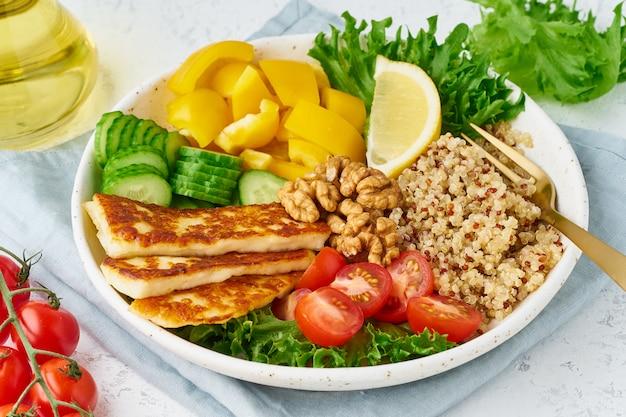 Tazón de buda con halloumi, quinoa, ensalada de lechuga, comida vegetariana, blanco, vista desde arriba