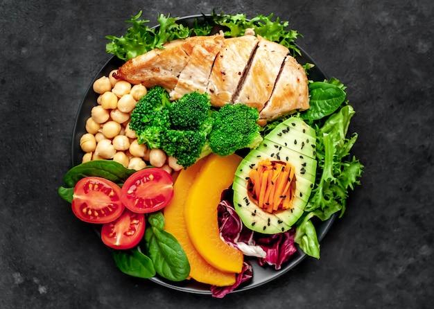 Tazón buda. pollo, brócoli, garbanzos, calabaza, aguacate, zanahoria, tomate, lechuga en un plato con cuchillo y tenedor