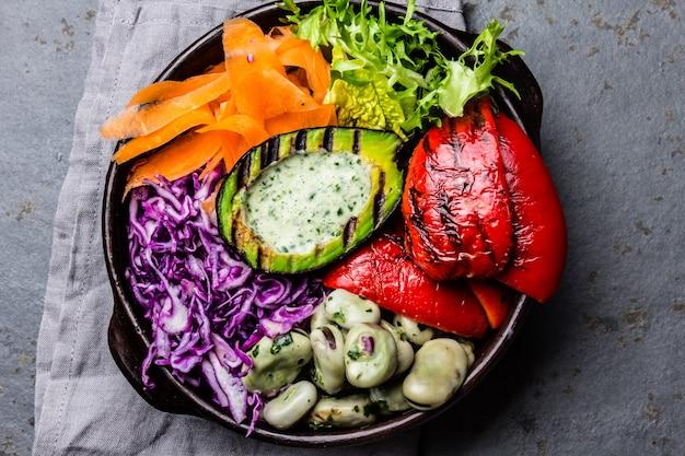 Tazón de budha. verduras crudas con las habas, el aguacate asado a la parrilla y el paprika en fondo de la pizarra.