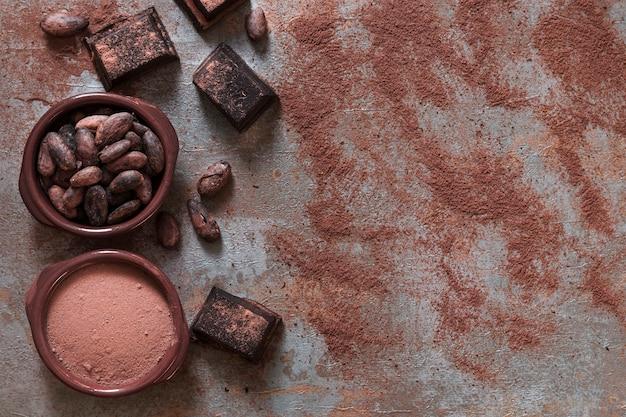 Tazón de cacao en polvo y frijoles con trozos de chocolate
