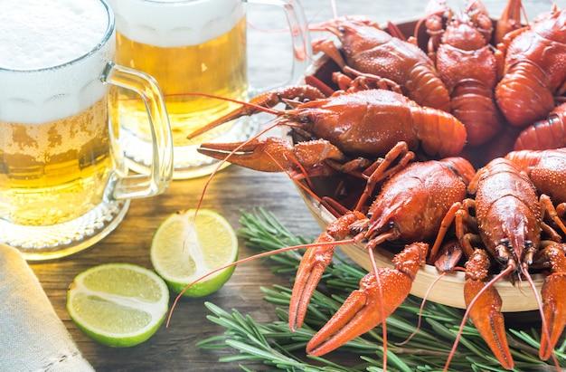 Tazón de cangrejo hervido con dos jarras de cerveza