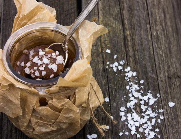 Tazón con caramelo salado y dulces sobre fondo de madera, espacio para texto