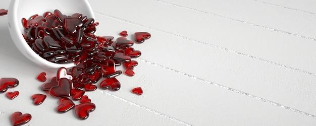Tazón con caramelos rojos con forma de corazón en madera blanca