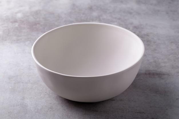 Tazón de cerámica blanco en blanco vacío en tablero de cemento