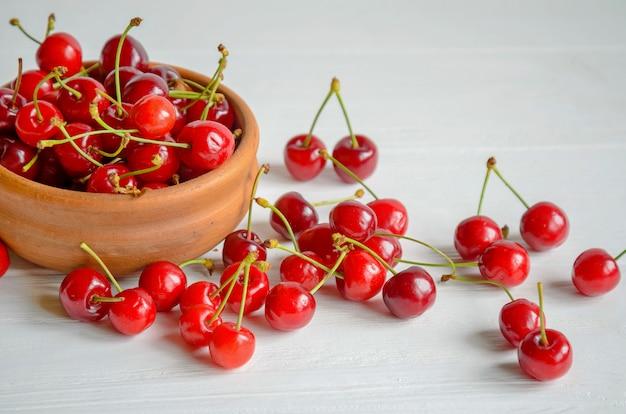 Tazón de cerámica marrón de cerezas frescas y sabrosas en madera blanca