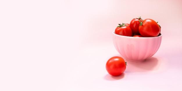 Tazón de cerámica rosa con tomates rojos maduros sobre un fondo rosa. dieta saludable vitaminas bio alimentos