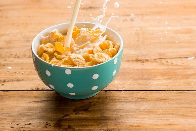 Tazón de cereal con chorro de leche en la mesa de madera