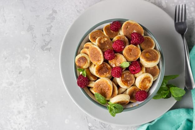 Tazón con cereal de panqueque pequeño con frambuesas, menta y mermelada