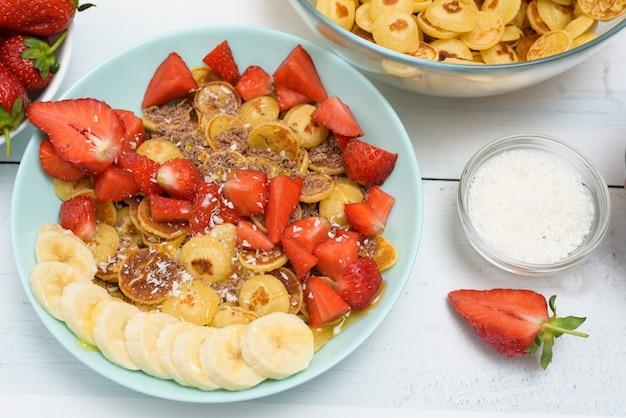 Tazón de cereal de panqueque pequeño con fresas frescas chocolate de plátano, virutas de coco y miel en pequeños platos.