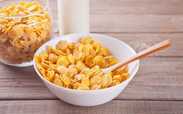 Un tazón de cereal seco de copos de maíz sobre madera