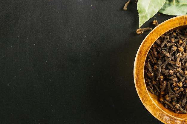 Tazón con clavos cerca de hojas de laurel