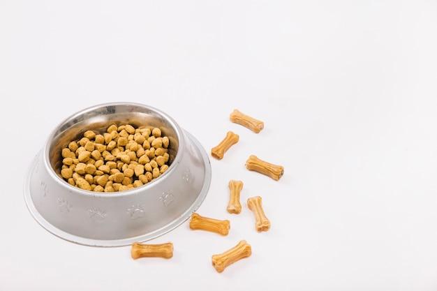 Tazón con comida cerca de masticar huesos