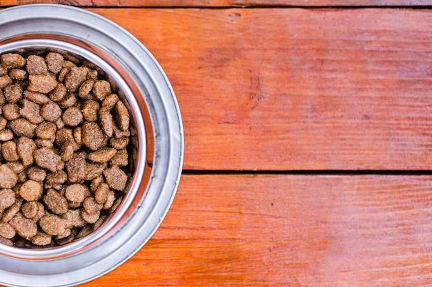 Tazón de comida para perros completo sobre fondo de madera con espacio de copia