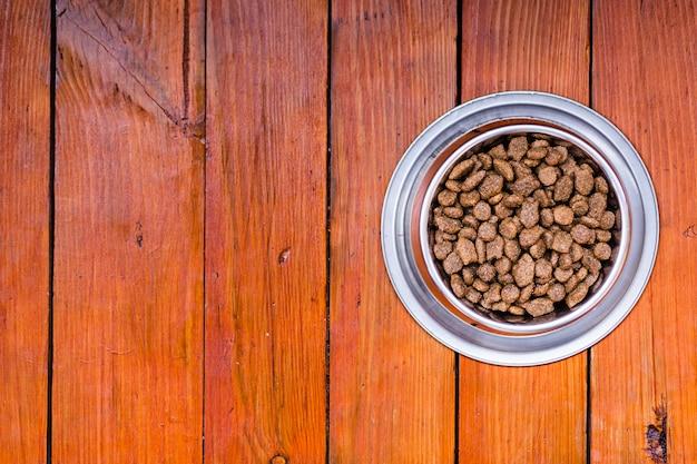 Tazón de comida para perros sobre fondo de madera con espacio de copia
