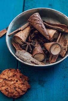 Un tazón con conos de waffle y especias dentro y una galleta en la mesa azul.