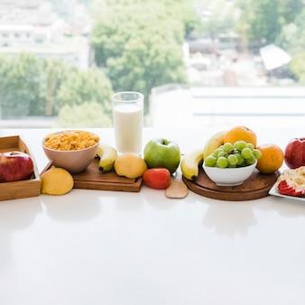 Tazón de copo de maíz y frutas coloridas con vaso de leche en mesa blanca cerca de la ventana