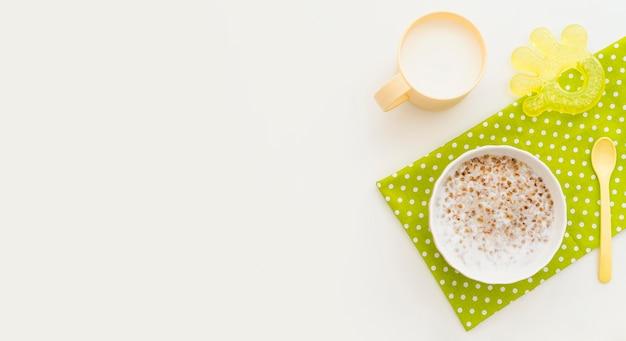Tazón con copos de avena y vaso de leche con espacio de copia