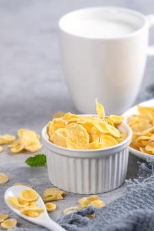 Tazón de copos de maíz dulces con leche sobre fondo de cemento gris, cerrar