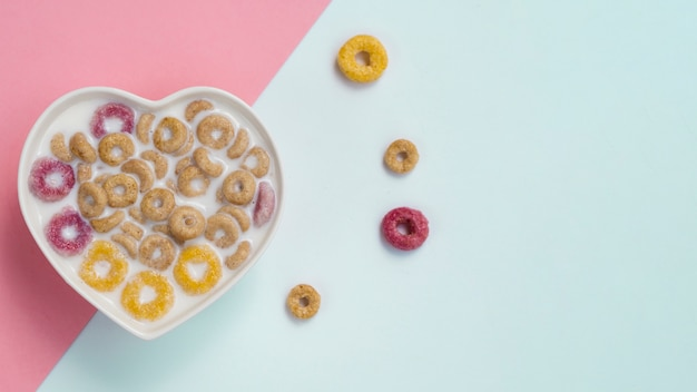 Tazón de corazón con copos de maíz y aros de frutas