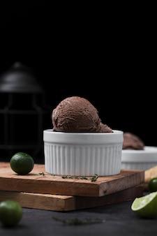 Tazón con cuchara de helado en bandeja de madera