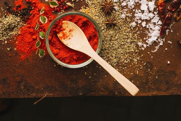 Tazón y cuchara con pimentón cerca de especias
