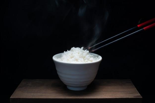 Tazón de arroz y palillos en la madera con vapor, fondo negro