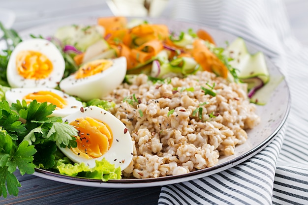 Tazón de desayuno con avena, calabacín, lechuga, zanahoria y huevo cocido