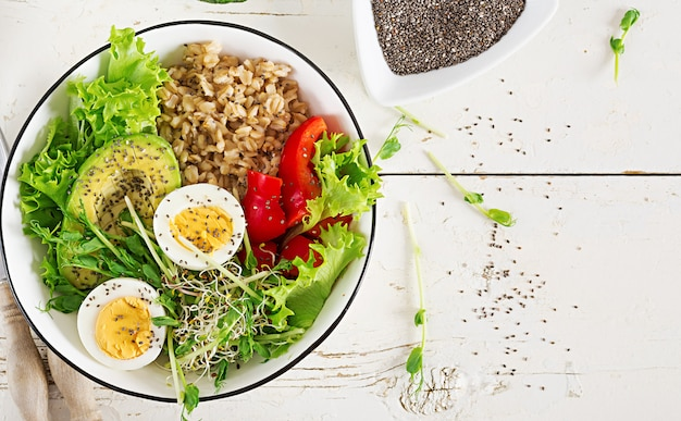 Tazón de desayuno con avena, pimentón, aguacate, lechuga, microgreens y huevo cocido.