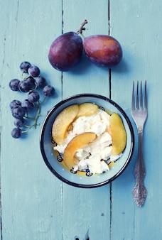 Tazón de desayuno saludable con ciruelas, uvas y queso crema.