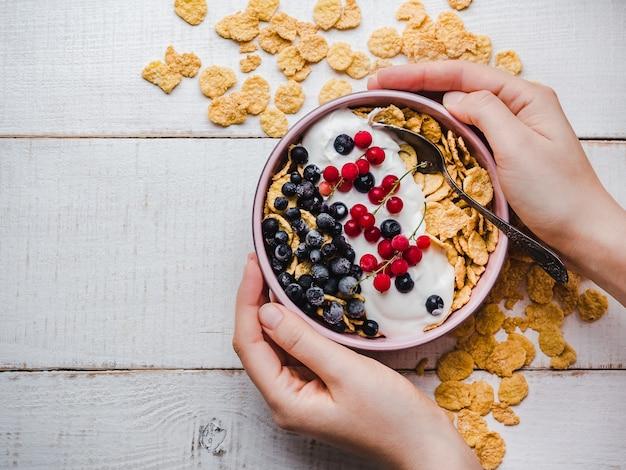 Tazón con desayuno saludable en las manos.