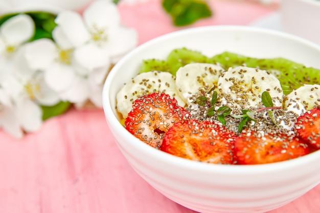 Tazón de desayuno saludable con semillas de fresa, plátano, kiwi y chía