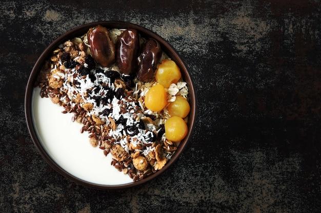 Tazón de desayuno con yogur griego, avena, granola y frutos secos.