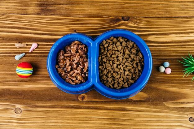 Tazón doble con comida para mascotas en superficie de madera.
