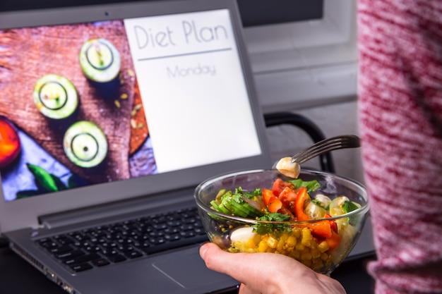 Tazón de ensalada de verduras en manos femeninas cerca de la computadora portátil en el escritorio