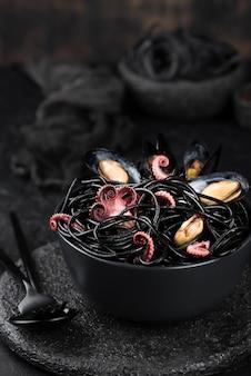 Tazón con espagueti negro y mejillones