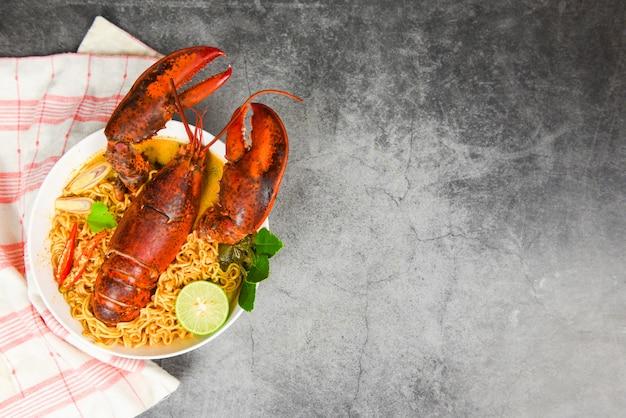 Tazón de fideos sopa picante de langosta marisco cocido con sopa de fideos instantáneos mesa de cena de langosta e ingredientes de especias en plato negro comida tailandesa