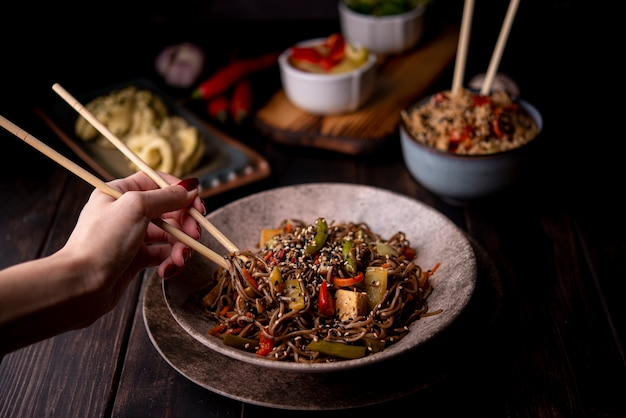 Tazón de fideos con verduras y otra comida asiática