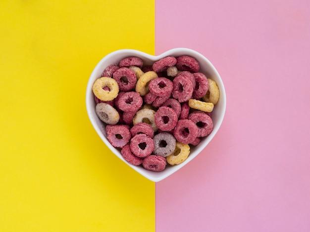 Tazón en forma de corazón lleno de aros de frutas rosas y amarillas