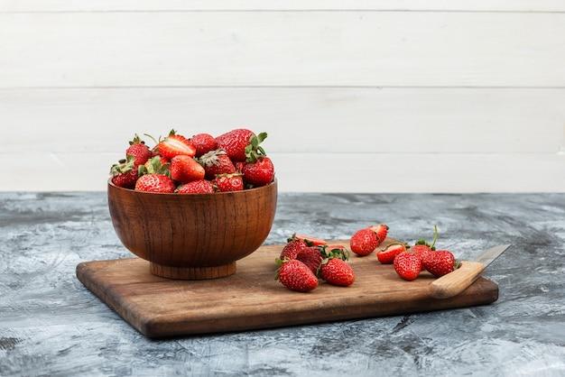 Un tazón de fresas y un cuchillo sobre una tabla de cortar de madera sobre un fondo de tablero de madera blanca y mármol azul oscuro. de cerca. espacio libre para tu texto