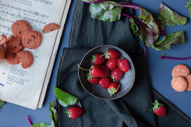 Tazón de fresas y galletas, hojas de espinaca, un libro sobre una estera negra.